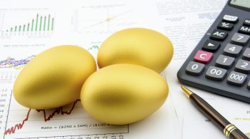 Three golden eggs with a calculator on business and financial reports : Investment concept