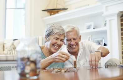 Cheerful senior couple counting coins at table